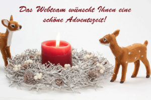 Das Webteam wünscht Ihnen eine schöne Adventszeit! Auf dem Bild ist ein Weihnachtsgesteck mit brennender Kerze zu sehen, daneben zwei Bambifigürchen.