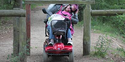 Symbolbild: Rollstuhlfahrer, der sich unter einer Barriere hindurchquält